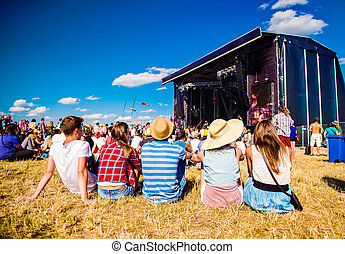 Teenagers, summer music festival, sitting in front of stage...