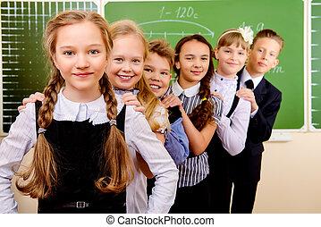teenagers uniform - Happy schoolchildren at a classroom. ...