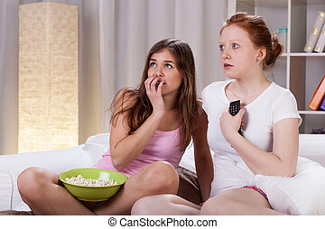 Teenagers watching horror movie on tv in evening