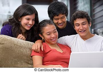 Teenagers watching something on laptop