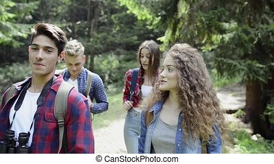 Teenagers with backpacks hiking in forest. Summer vacation....