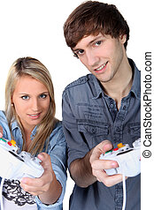 Teenagers with games console controllers