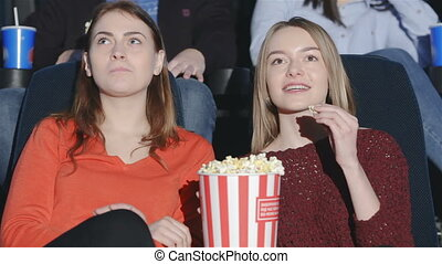 Teens are chewed popcorn with soda and enjoy movies