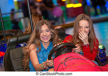 teens at fun fair riding dodgems or bumper cars.