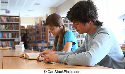 Teens at library - Boy and girl studying at library then...