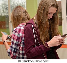 Teens communicate with mobile phone - Zwei Freundinnen...
