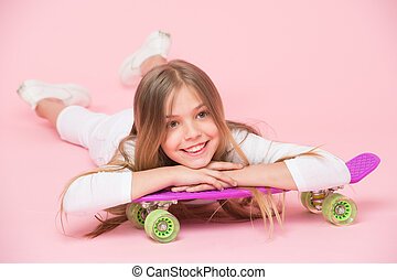 Teens hobby concept. Girl likes to ride skateboard and sporty lifestyle. Girl on smiling face posing with penny board, pink background. Kid girl with long hair ready to ride penny board