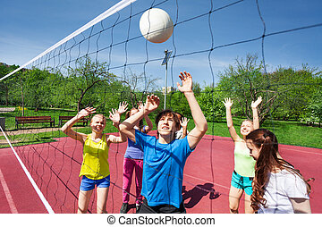 Teens in motion with arms up try to catch ball near net on the volleyball playing court during sunny summer day