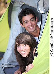 Teens leaning in tent