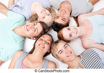 Teens lying on floor with heads together