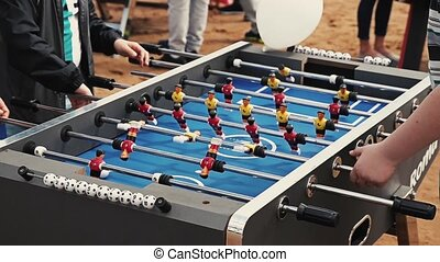 Teens play american table soccer. Field of a game focus in. Summer festival