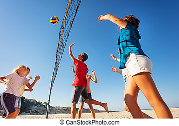 Teens playing volleyball during summer vacation
