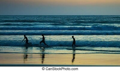 Teens playing with a ball in the tropical sea waves at sunset