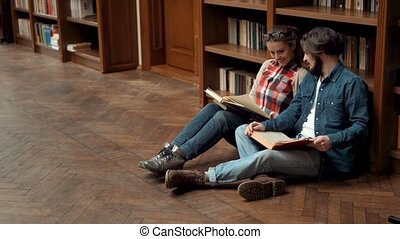 Teens Read Books on Floor - Two teens reading books while...