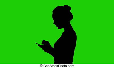 Teen's silhouette with smartphone on green background