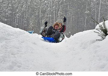 Teens sledding on a saucer