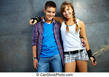 Teens - Couple of happy teens looking at camera outside