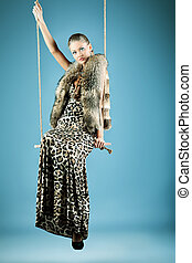 teeter - Charming young woman on a swing. Studio shot.