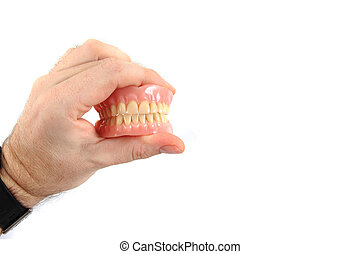 teeth prosthesis in human hand isolated on the white ...