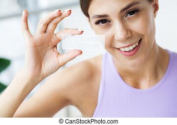 Teeth whitening, beautiful smiling woman holding a whitening strip