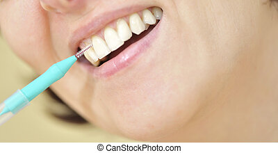 Teeth with an interdental brush - woman cleaning her teeth...