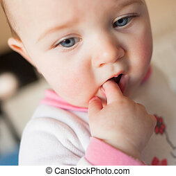 Teething concept. Baby girl with finger in mouth. - Eight...