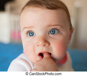 Teething concept. Baby girl with finger in mouth.