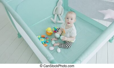 Teething infant biting toy eggs in playpen at home