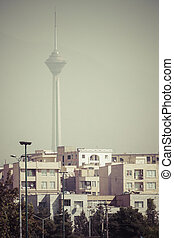TEHERAN, IRAN - OCTOBER 03, 2016: Residential buildings in front of Milad Tower in air-polluted skyline of Tehran illuminated with golden sunset.