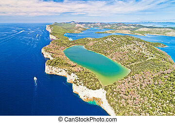 Telascica nature park cliffs and green Mir lake on Dugi Otok island aerial view, Kornati archipelago national park of Croatia