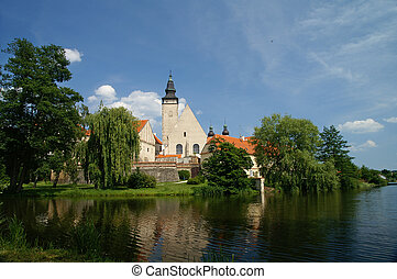 Telc - Baroque town with church steeple, across lake. Telc,...