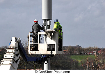 Telecommunication Mast Being Repair - Two workmen on a ...