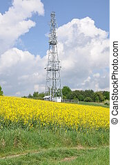 Telecommunication tower on the field against the sky