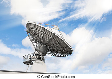 Telecommunications radar parabolic radio antenna as part of global communication technology stations system against sunny sky with sun rays sunbeams. Toned and filtered stock photo.