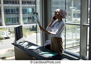 telefon, mischenrennen, beweglich, sprechende , weiblicher doktor, während, bericht, schauen, röntgenaufnahme, junger