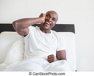 telefone, feliz, homem, cama, sentando