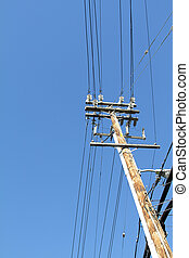 Telegraph pole over blue sky