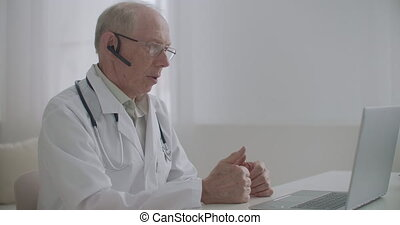 telemedicine session with cardiologist, aged male doctor is sitting in his medical office and chatting online with patient and colleague