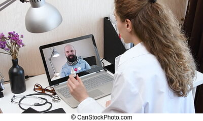 Telemedicine. Consultation with physician through mobile video call. Doctor talking to comlaining patient using video chat application on laptop and prescribes a medication