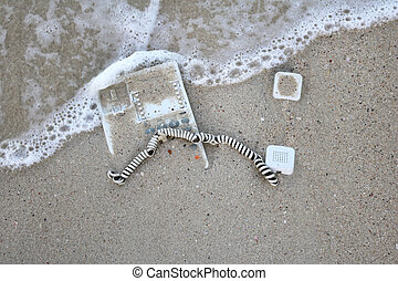 Desk phone in the sand on the beach