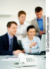 Telephone in the office with working business team in the...