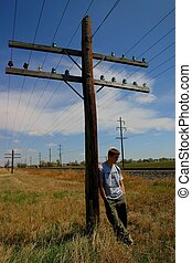 Boy leaning against very short telephone pole, typical of poles in Southeastern Colorado.