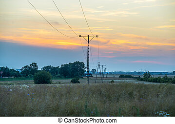 telephone pole in the field with transmission lines