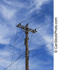 Utility lines and pole against a pretty blue sky with light clouds
