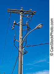 A convoluted mess of wires and cables clutter a wooden telephone pole and street lamp.