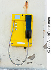 Telephone set mounted on a dilapidated wall