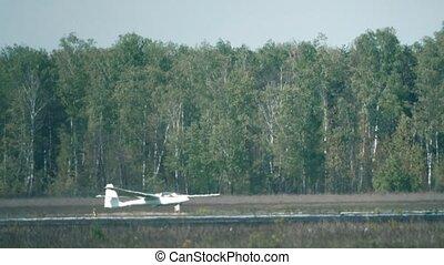 Telephoto lens shot of a glider landing beyond runway heat haze. 4K video