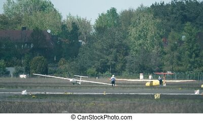 Telephoto lens shot of two men towing a glider on the ground...