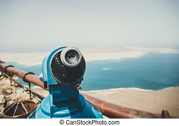 Telescope and panoramic view at La Graciosa Island from Mirador del Rio viewpoint.