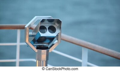 Telescope in metalic shell on deck of ship which floats in...
